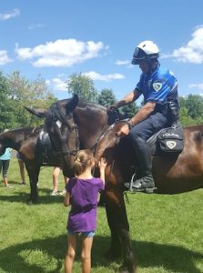 Friends of Madison Mounted Horse Patrol Facebook Page A Mounted Patrol officer handing out trading cards of the horses, which include information such as breed, age, height and weight.